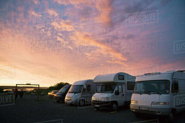 Vans parked on field against sky during sunset Royalty-free stock photo
