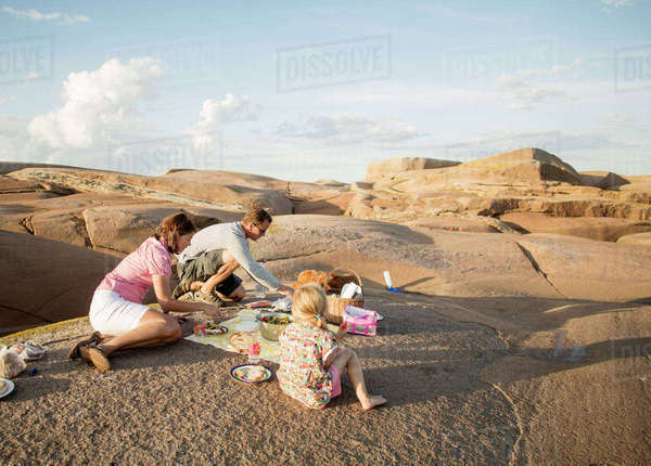 Family enjoying picnic on rock formation against sky Royalty-free stock photo