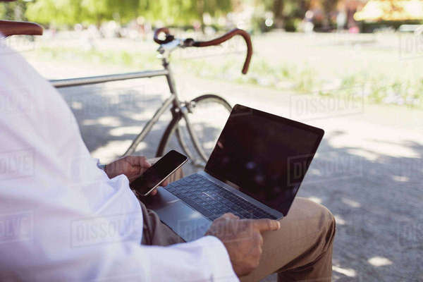 Midsection of businessman using laptop and smart phone while sitting on park bench Royalty-free stock photo