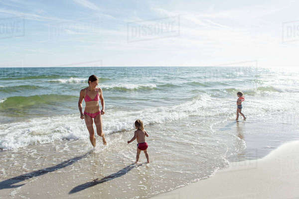 Mother and daughters enjoying on beach against sky during sunny day Royalty-free stock photo