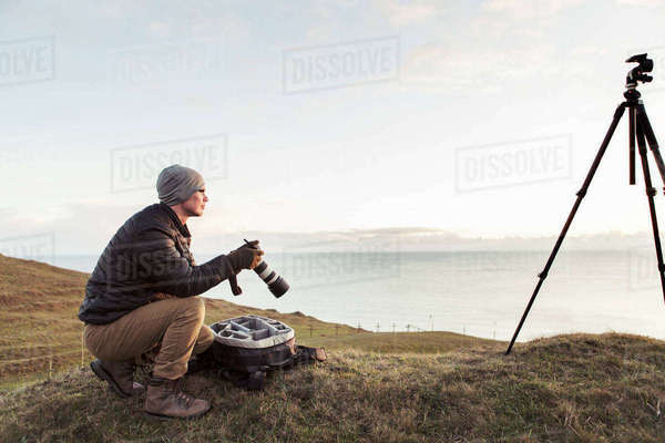 Side view of hiker looking away while holding SLR camera on hill by sea against sky Royalty-free stock photo