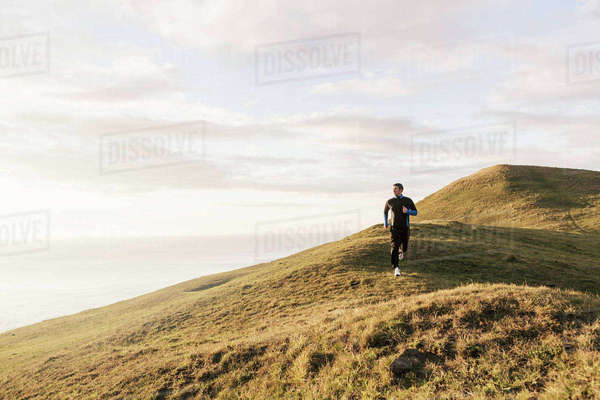 Man jogging on hill by sea during sunny day Royalty-free stock photo