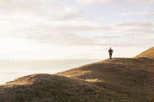 Mid distance of man jogging on hill by sea during sunny day Royalty-free stock photo