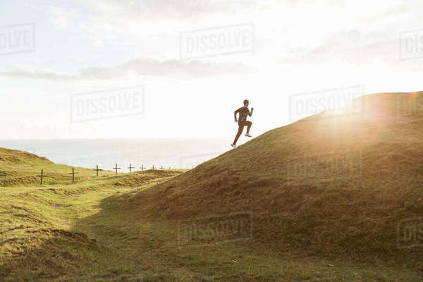 Mid distance of man jogging on grassy hill during sunny day Royalty-free stock photo