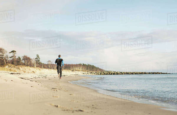Rear view of man jogging on shore at beach against cloudy sky Royalty-free stock photo