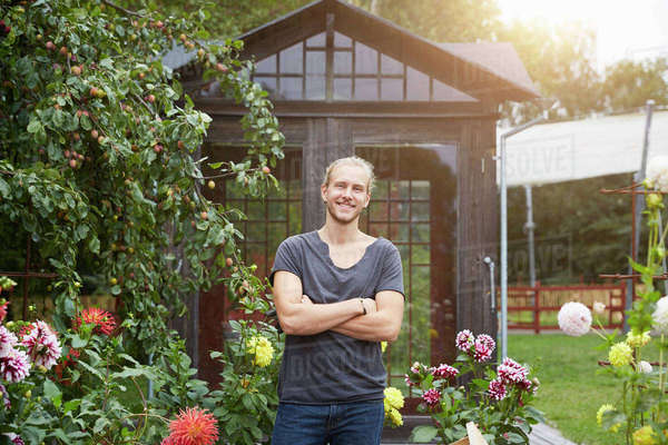 Portrait of male gardener with arms crossed smiling in yard Royalty-free stock photo
