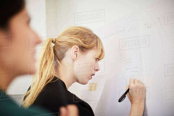 Side view of mid adult businesswoman writing on whiteboard with colleague in foreground at office Royalty-free stock photo