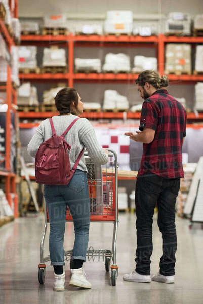 Full length rear view of couple discussing while walking in hardware store Royalty-free stock photo