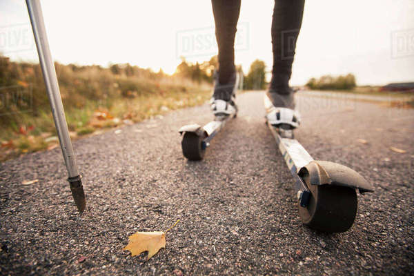 Low section of man roller skiing on country road Royalty-free stock photo