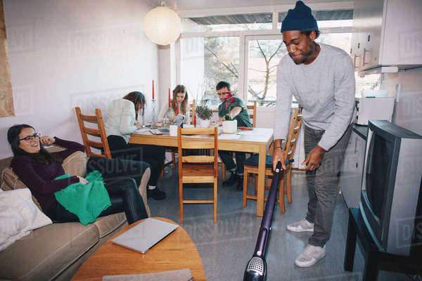 Man cleaning floor while friends sitting in college dorm room Royalty-free stock photo