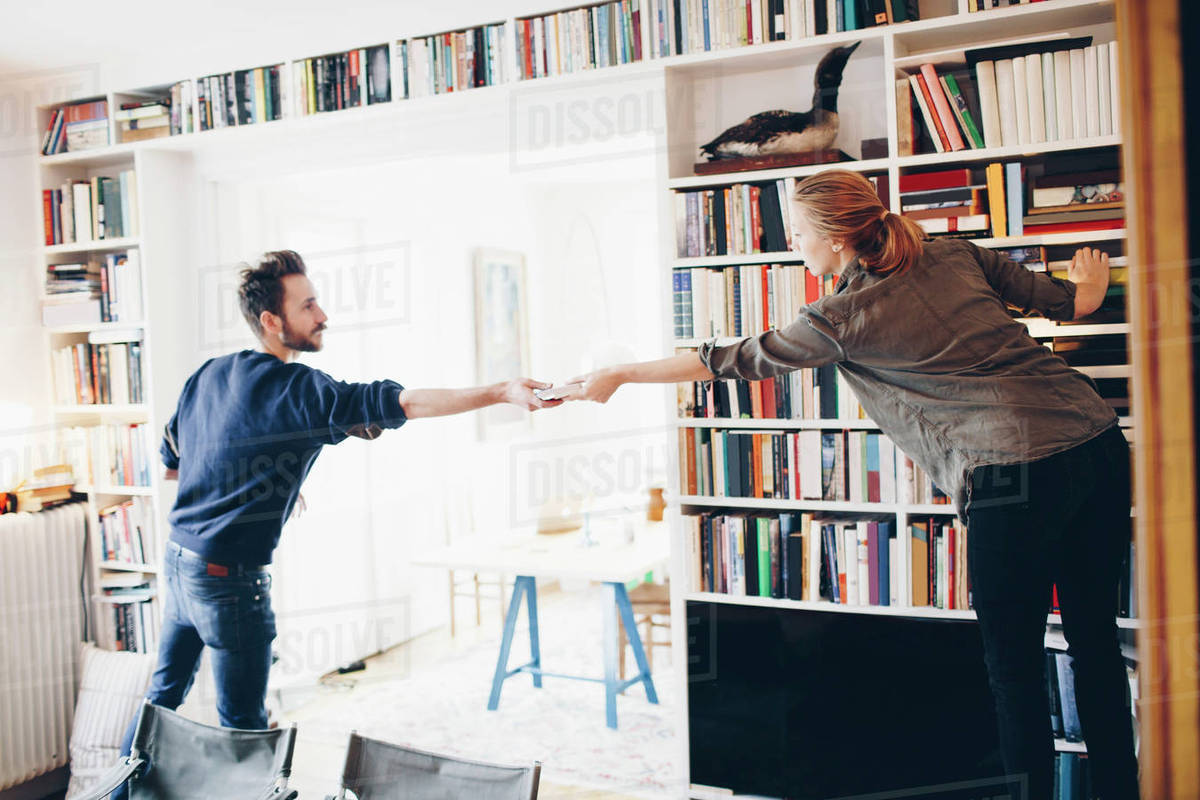 Rear View Of Man Giving Book To Woman Standing Against Bookshelf At Home