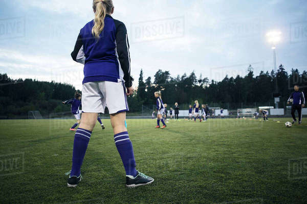 Rear view of girl looking at players playing on soccer field Royalty-free stock photo