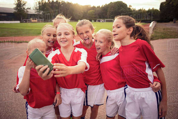 Cheerful soccer girls taking selfie on footpath against field Royalty-free stock photo