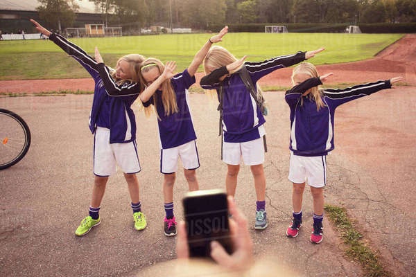 Cropped girl photographing friends performing dab dance on footpath against soccer field Royalty-free stock photo