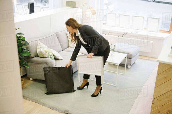 High angle view of female realtor holding sign by sofa in office Royalty-free stock photo