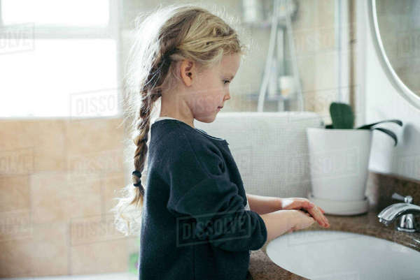 Side view of girl washing hands at sink in bathroom Royalty-free stock photo