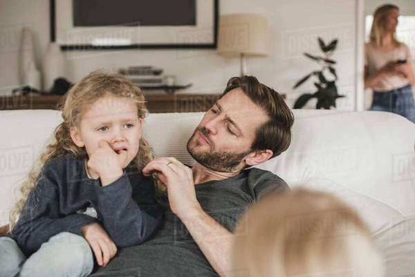 Mid adult man looking at daughter sitting on sofa at home Royalty-free stock photo