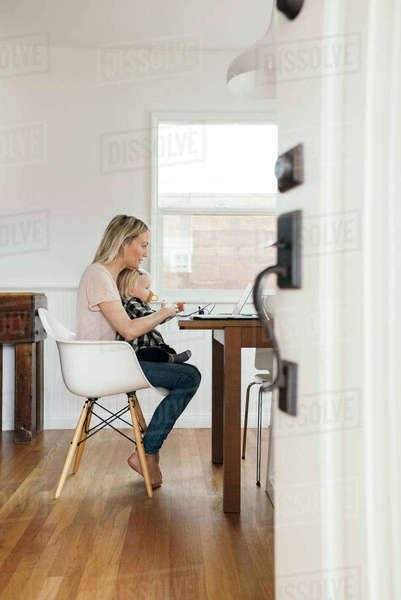 Full length side view of woman with daughter using laptop at home Royalty-free stock photo