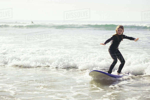 Full length of girl surfing in sea Royalty-free stock photo