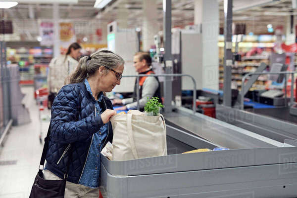 Smiling mature woman holding bag at checkout counter in supermarket Royalty-free stock photo