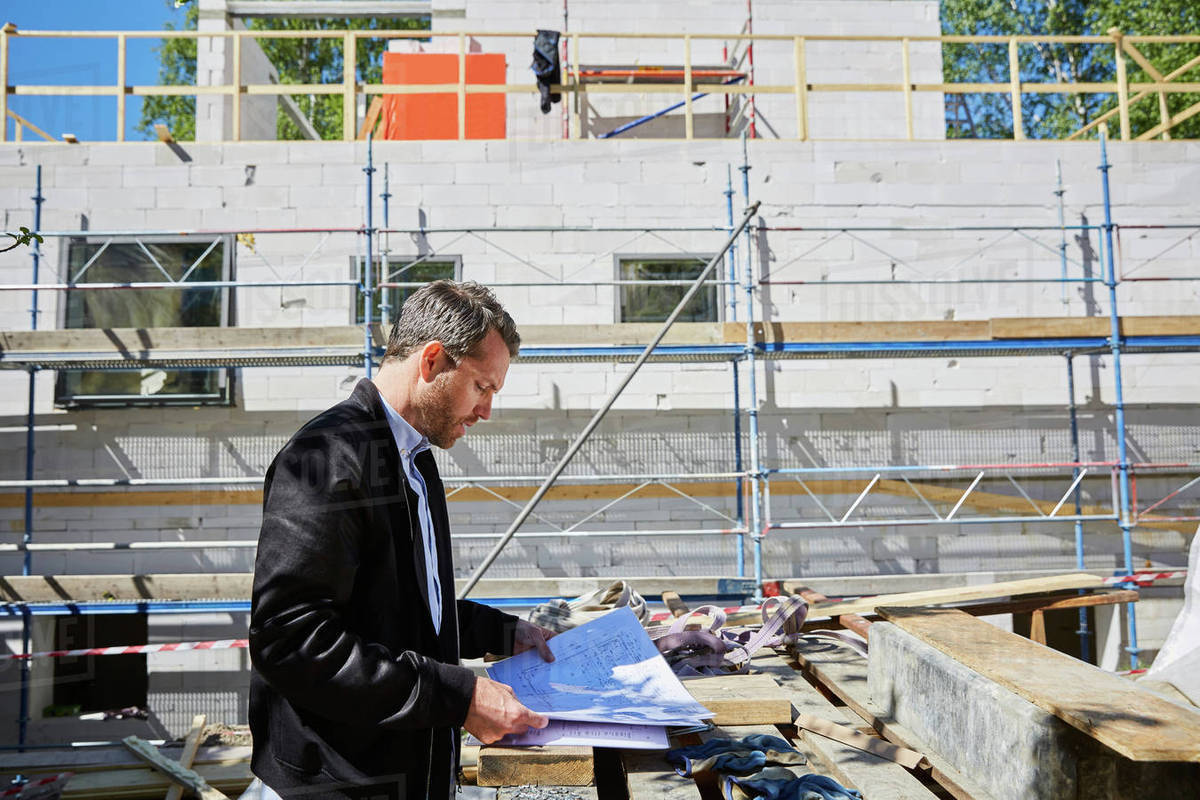Side view of architect reading blueprint by incomplete building at side view of architect reading blueprint by incomplete building at construction site malvernweather Images