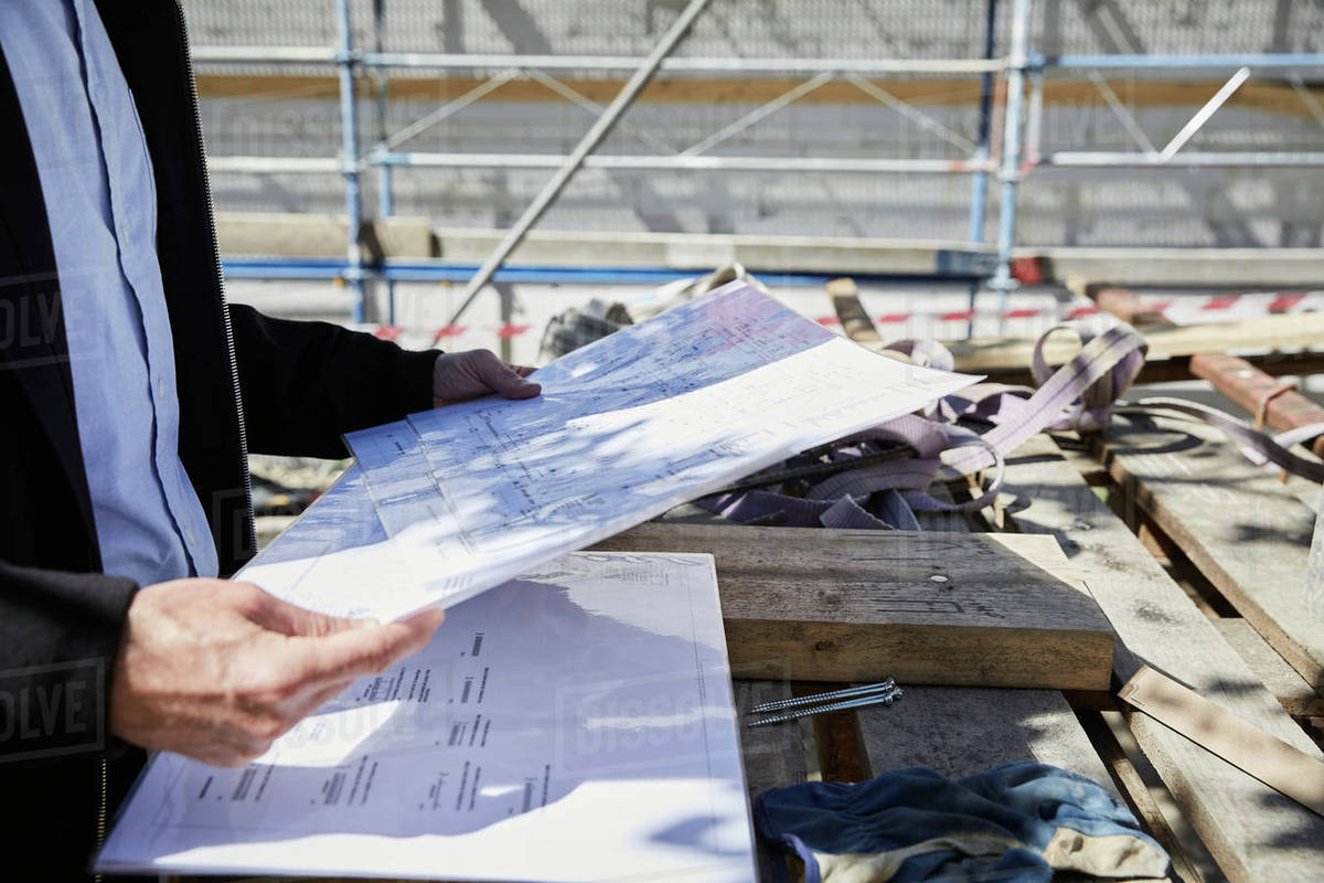 Midsection of architect with blueprint on table at construction site midsection of architect with blueprint on table at construction site malvernweather Image collections
