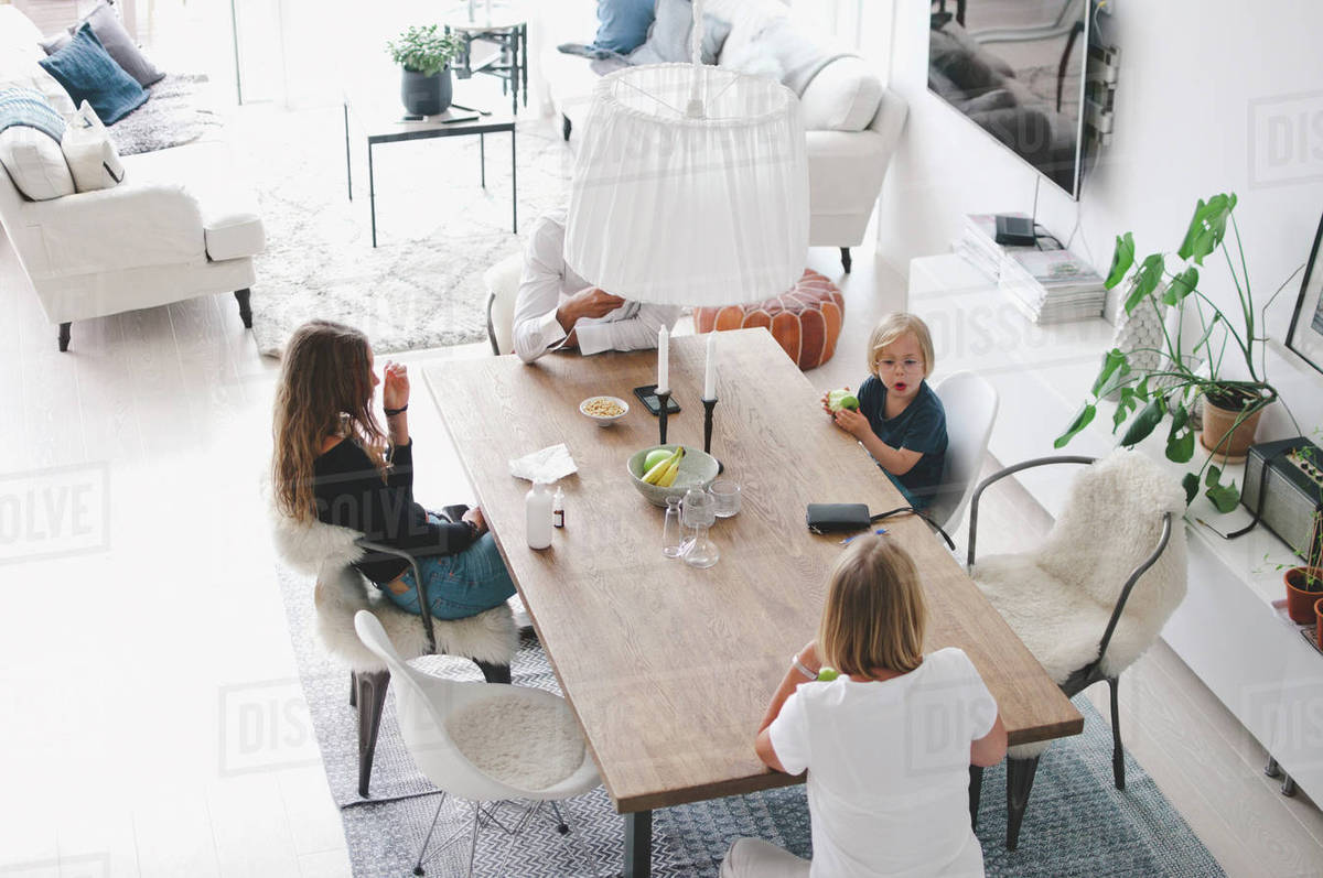 High angle view of family sitting at table in living room - Stock ...