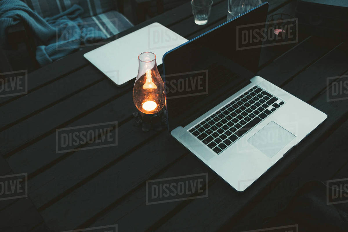 High angle view of laptops on wooden table at holiday villa during sunset  stock photo