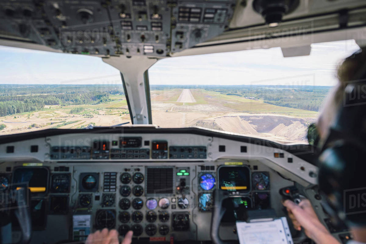 Cropped image of pilot flying airplane using control panel over landscape  stock photo