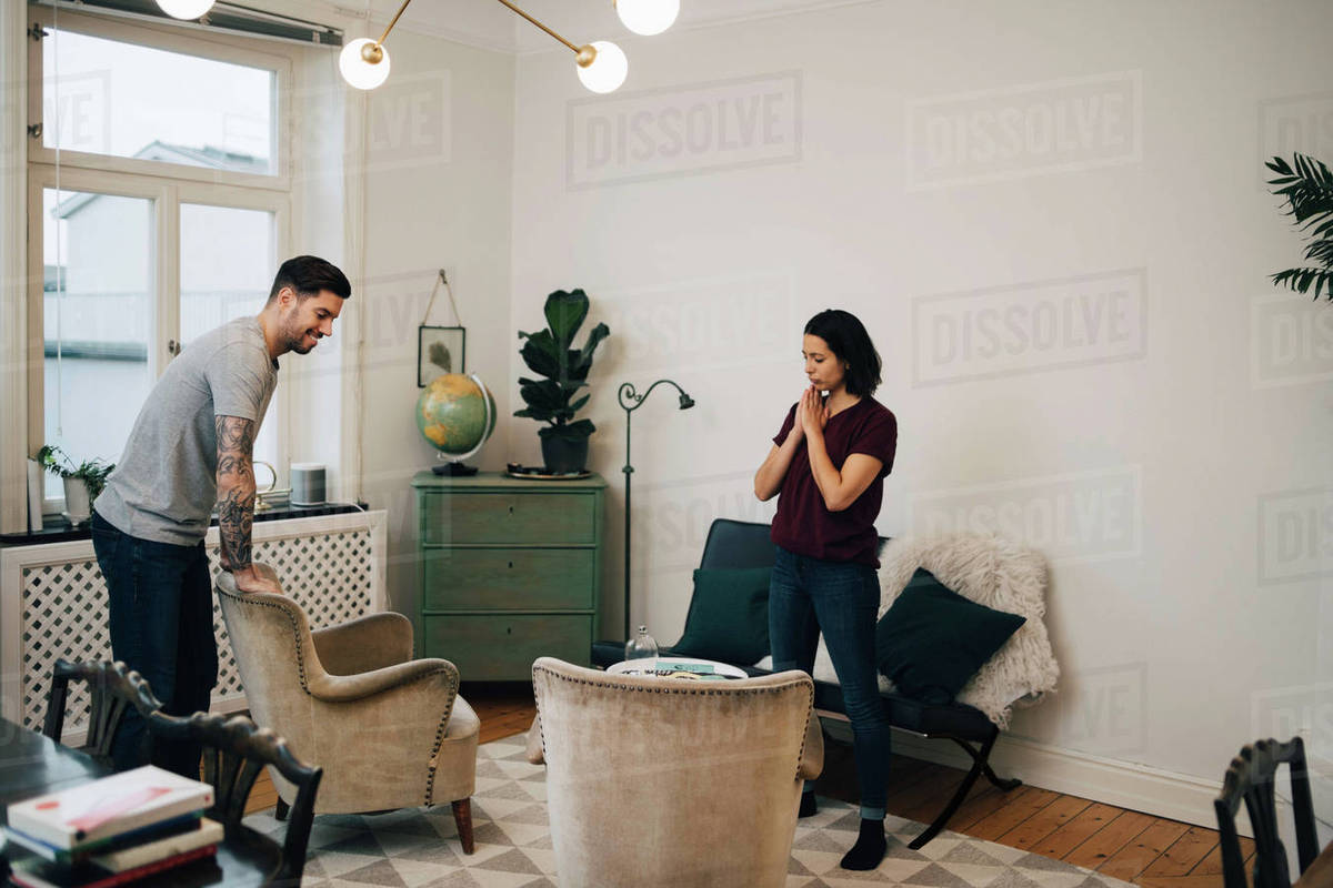 Full length of man and woman arranging sofa in living D929_46_094