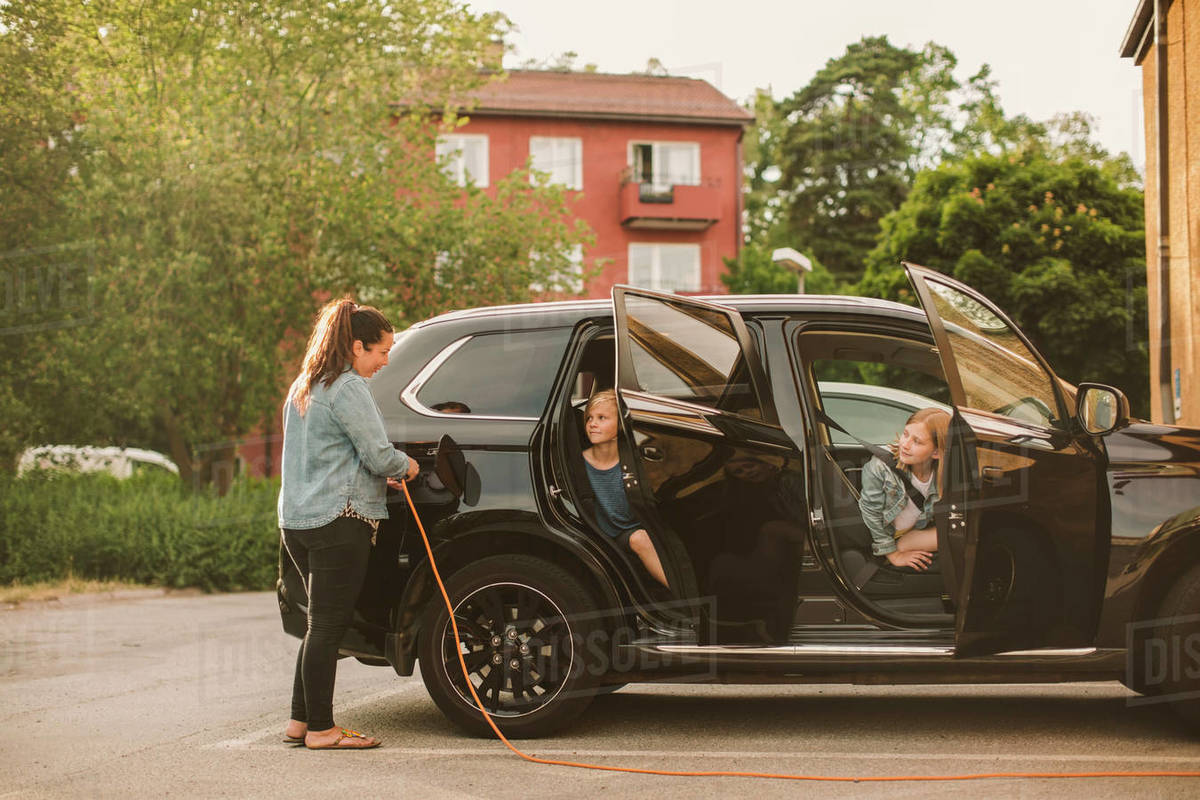 Girls looking at smiling mother charging electric car at station Royalty-free stock photo