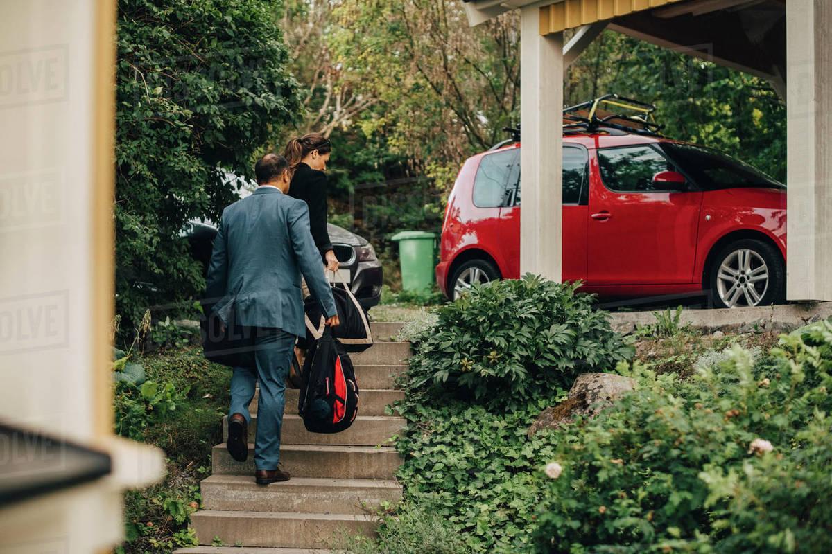Rear view of business couple walking towards cars at holiday villa Royalty-free stock photo