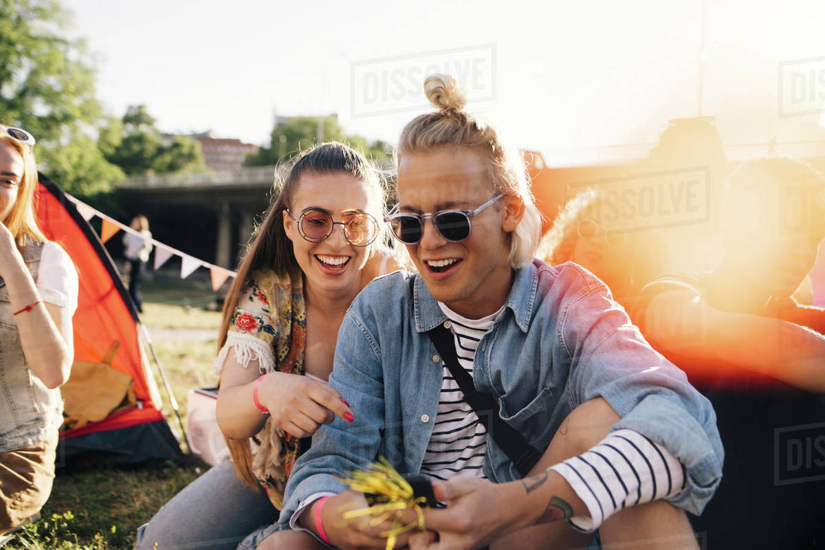 Smiling male and female friends looking at smart phone while sitting on lawn in sunny day Royalty-free stock photo
