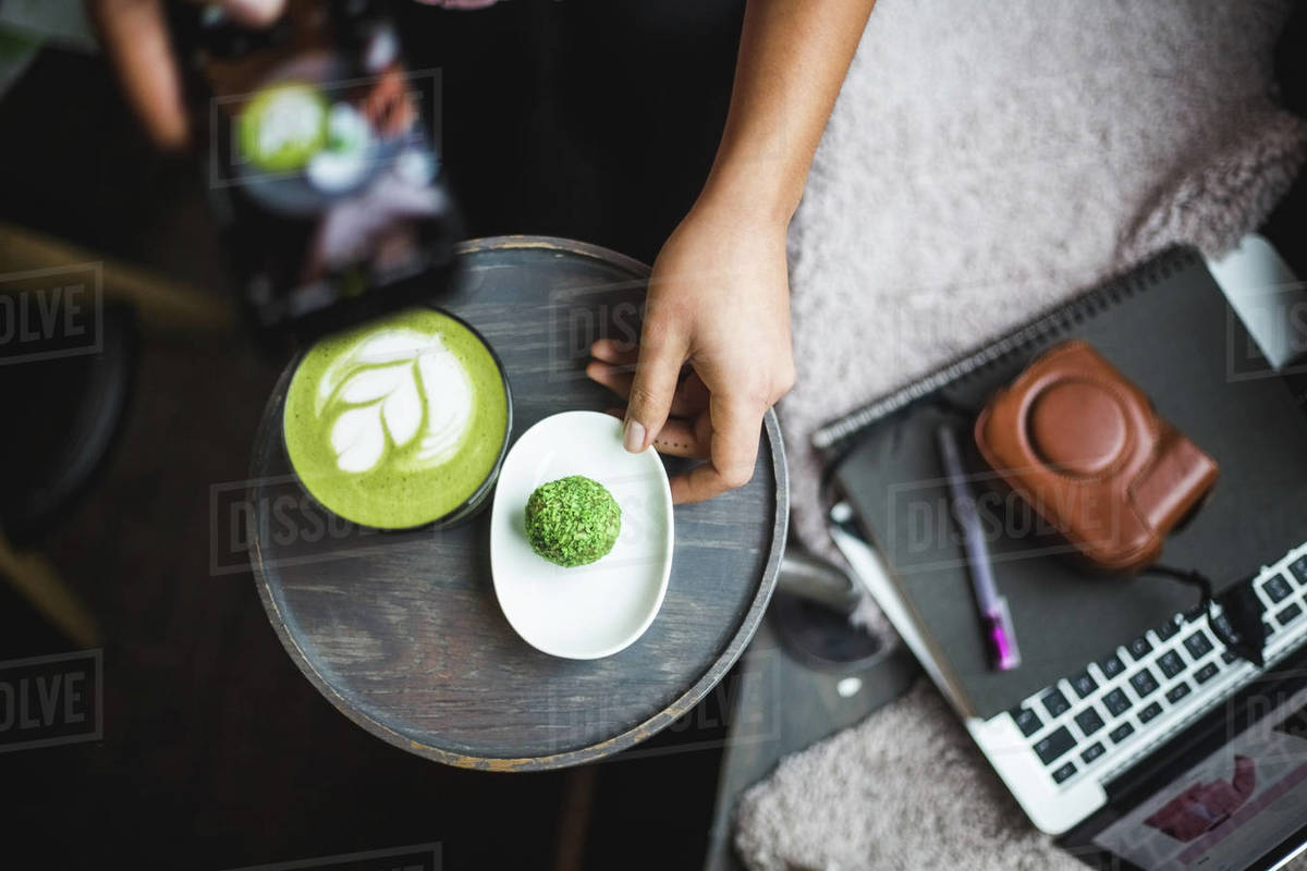 Directly above view of female blogger photographing matcha tea and snack through smart phone at creative office Royalty-free stock photo