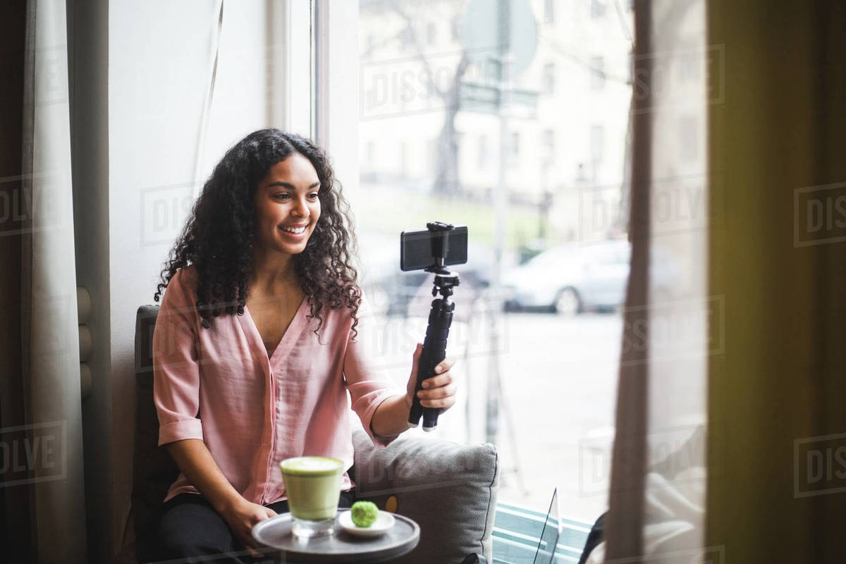 Confident young female influencer vlogging through mobile phone on tripod sitting by window at creative office Royalty-free stock photo