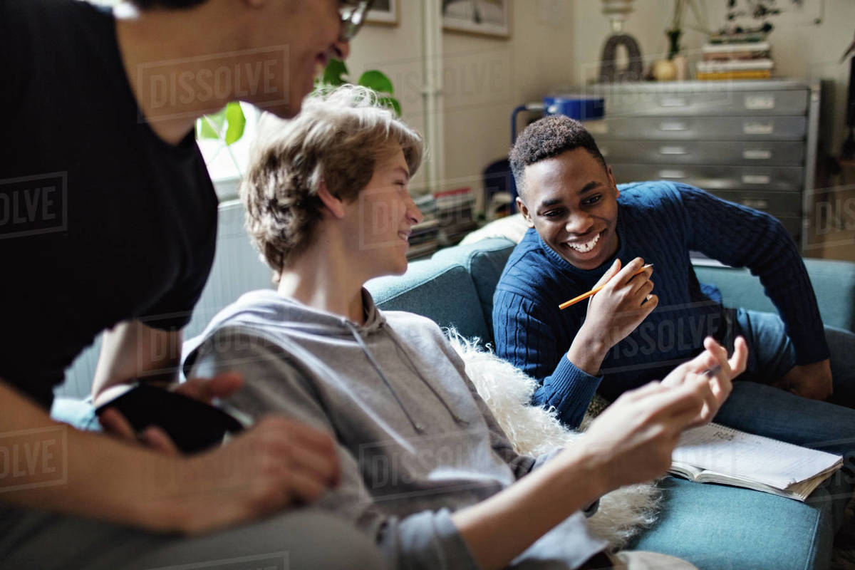 Smiling teenage boy showing mobile phone to friends on sofa while studying at home Royalty-free stock photo
