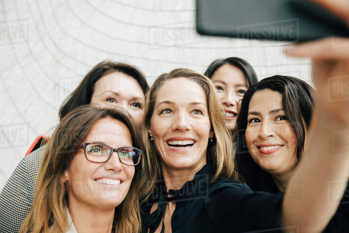 Smiling businesswoman taking selfie with female professionals at office during conference event Royalty-free stock photo