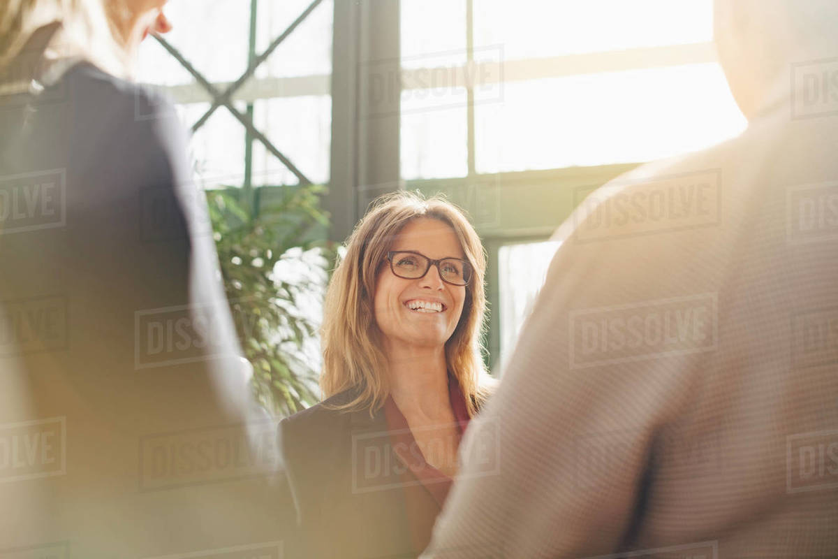 Smiling mature businesswoman discussing with colleagues in meeting Royalty-free stock photo
