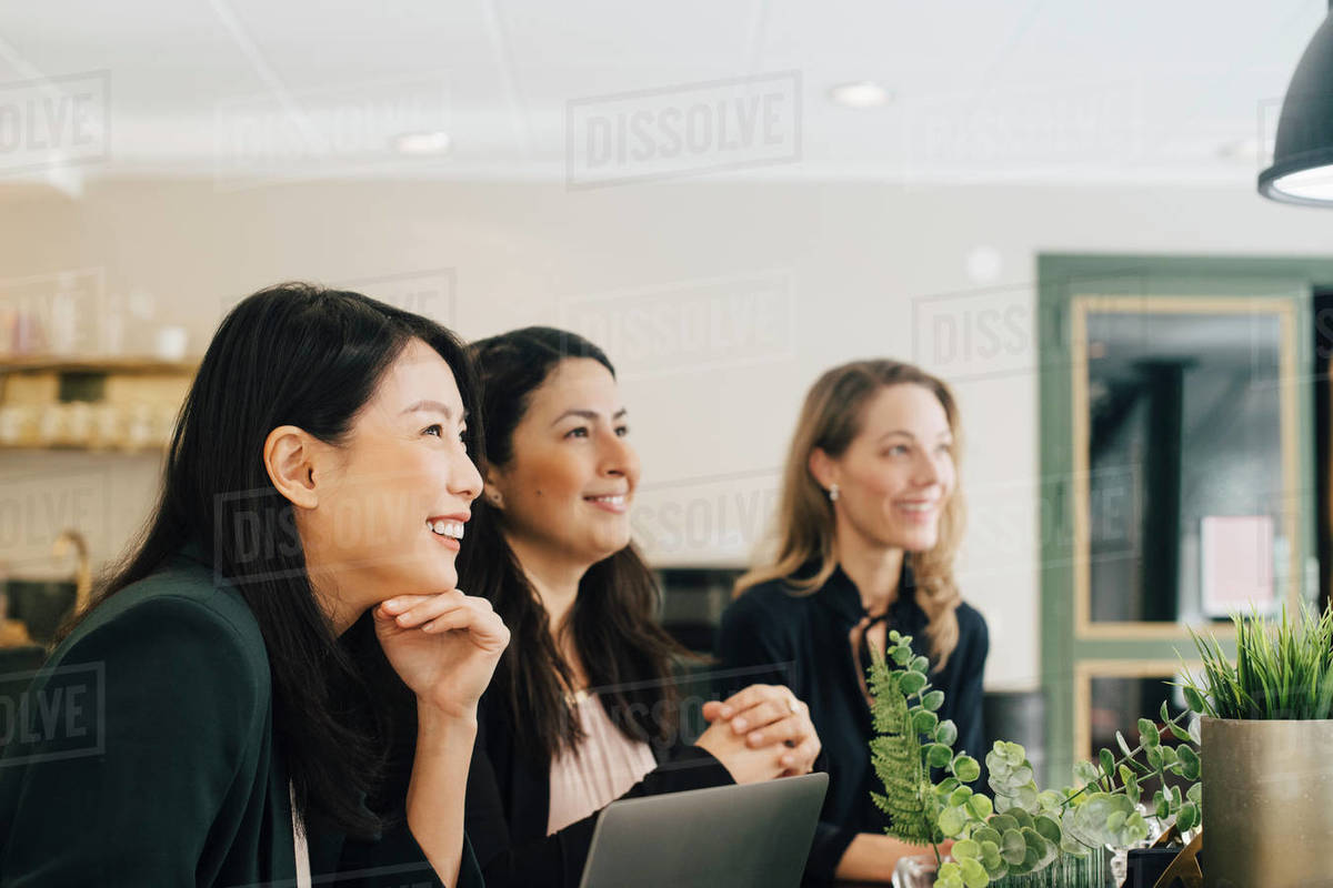 Smiling businesswomen sitting at conference table in meeting Royalty-free stock photo