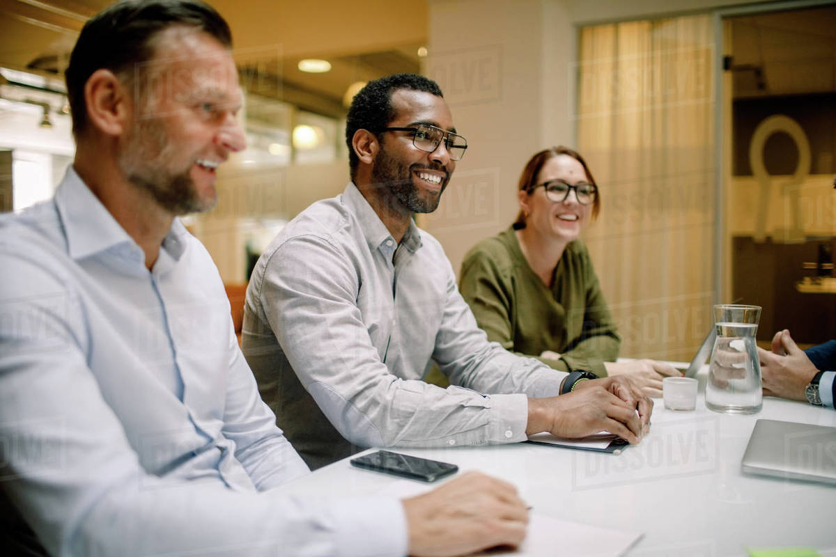 Sales executives smiling during business meeting at conference table in office Royalty-free stock photo