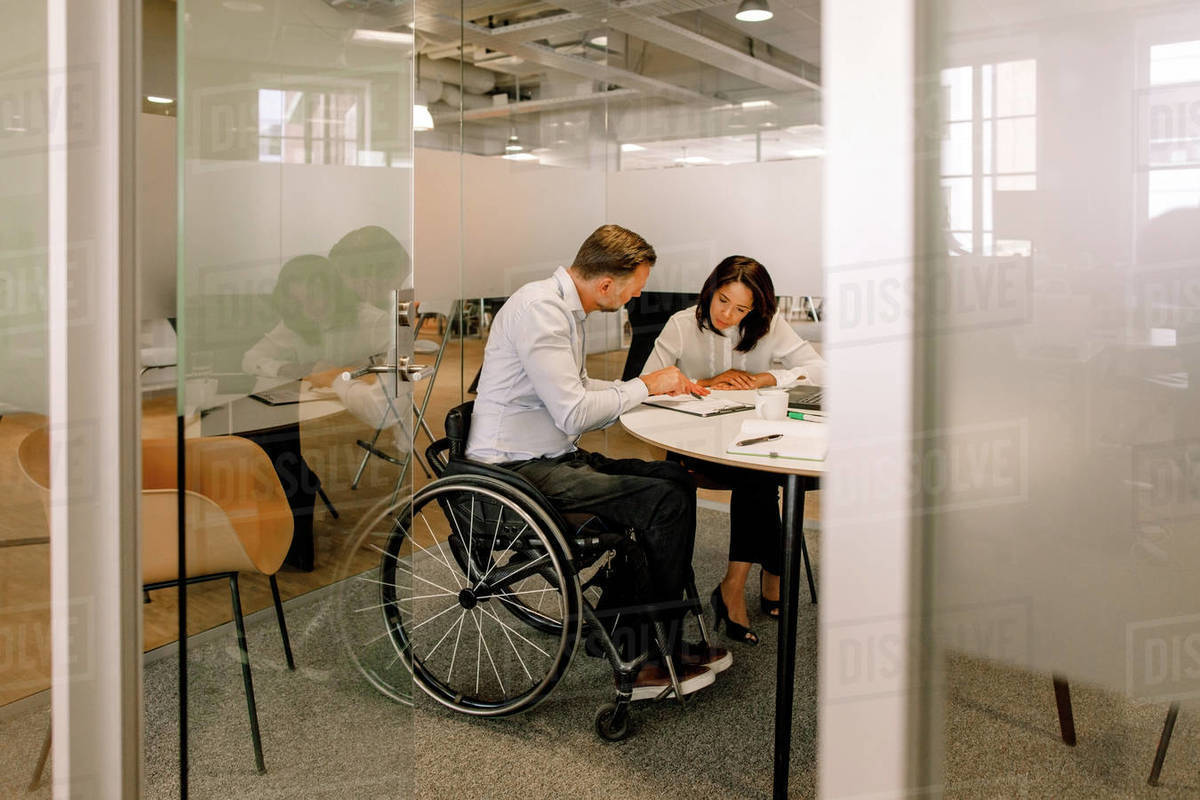 Serious female manager and disabled businessman working in board room Royalty-free stock photo