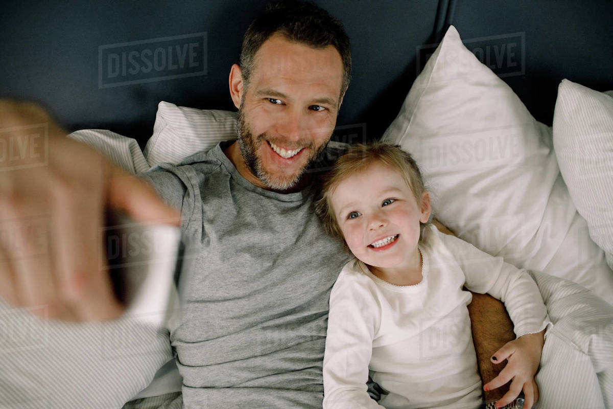 High angle view of happy father taking selfie with smiling daughter on bed in hotel Royalty-free stock photo