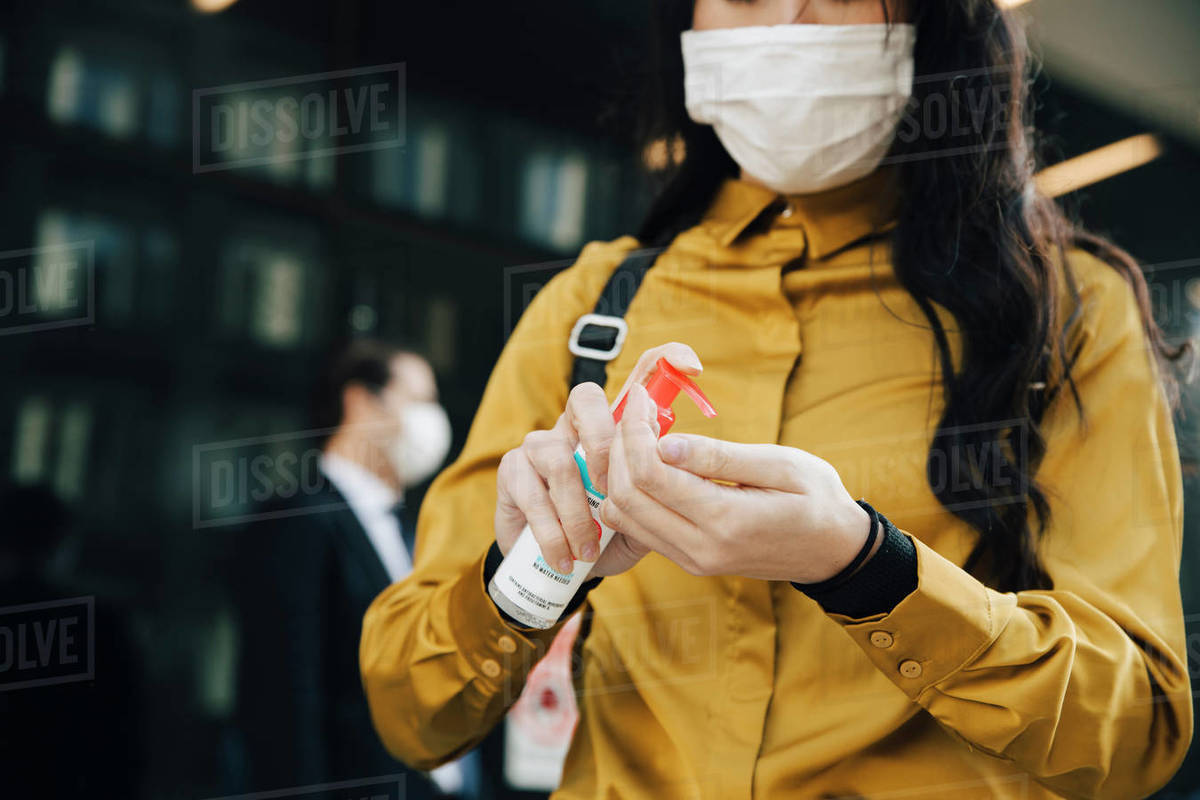 Woman with face mask applying hand gel Royalty-free stock photo