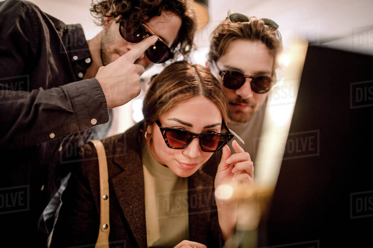 Smiling friends trying fashionable eyeglasses at store Royalty-free stock photo