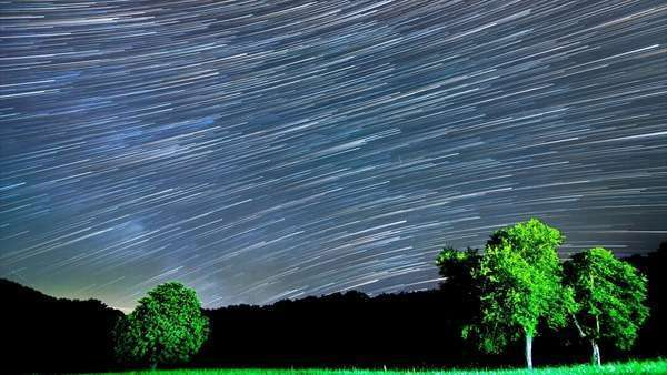 Milky Way star trails, timelapse of stars and Milky Way over a field with trees Royalty-free stock video