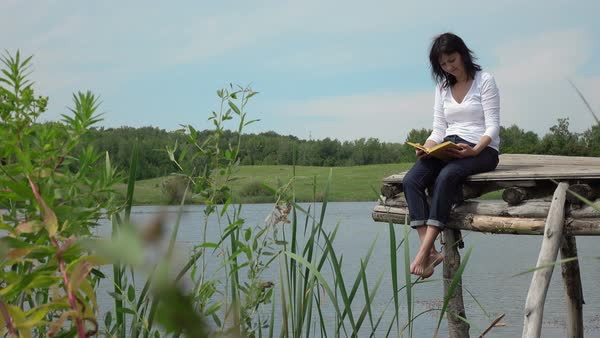 Woman reading book on the pier near lake. - Stock Video Footage - Dissolve