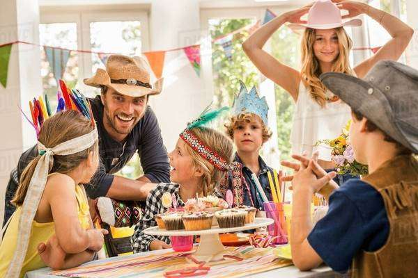 Parents and children laughing and chatting at kids birthday party Royalty-free stock photo