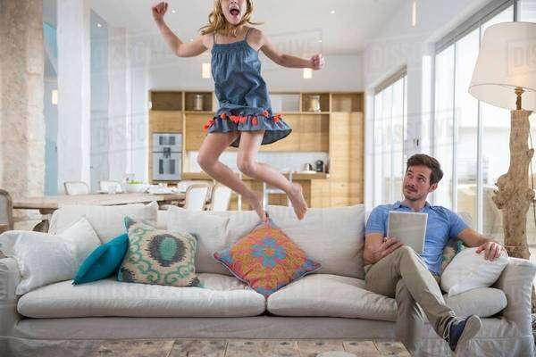 Girl jumping mid air from living room sofa whilst father uses digital tablet Royalty-free stock photo