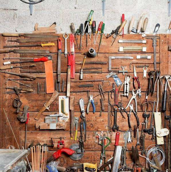 Variety of hand tools displayed on workshop wall Royalty-free stock photo