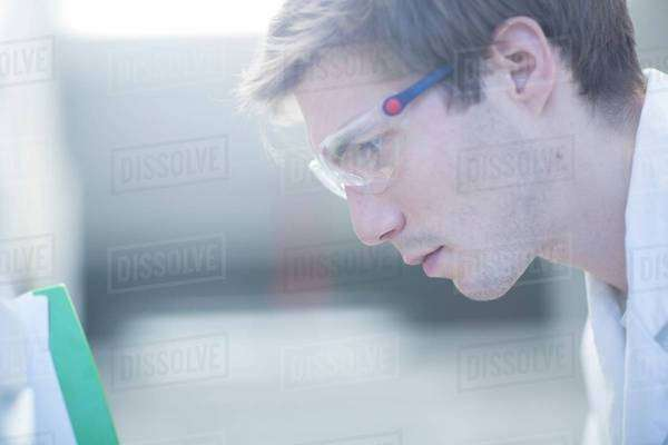 Close up of male scientist reading papers in lab Royalty-free stock photo